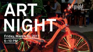 Cover photo of orange-colored bicycle lit up with tiny white lights to promote Art Night March 2017