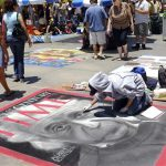 Graphic designer from Japan, Moe Notsu draws with chalk a Time Magazine cover of Albert Einstein along the street during the Pasadena Chalk Art Festival in Pasadena, Calif. on Sunday June 17,2012. (AP Photo/Richard Vogel)