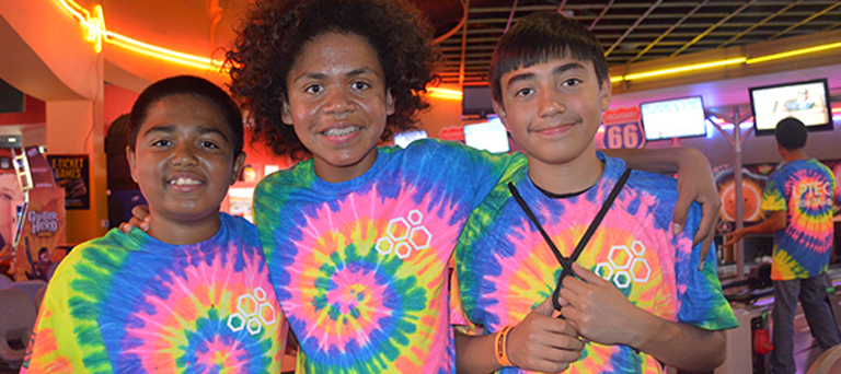 Three teens posed wearing tie-dyed tshirts