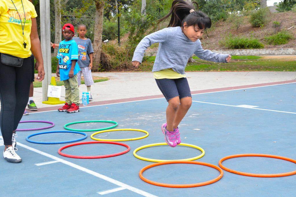 Girl jumping over hula hoops at Neighborhood Camps