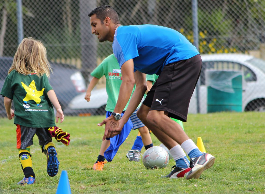 Image of Instructor and kids playing soccer