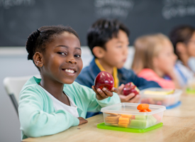 Child Eating Apple at Desk 200x275 image