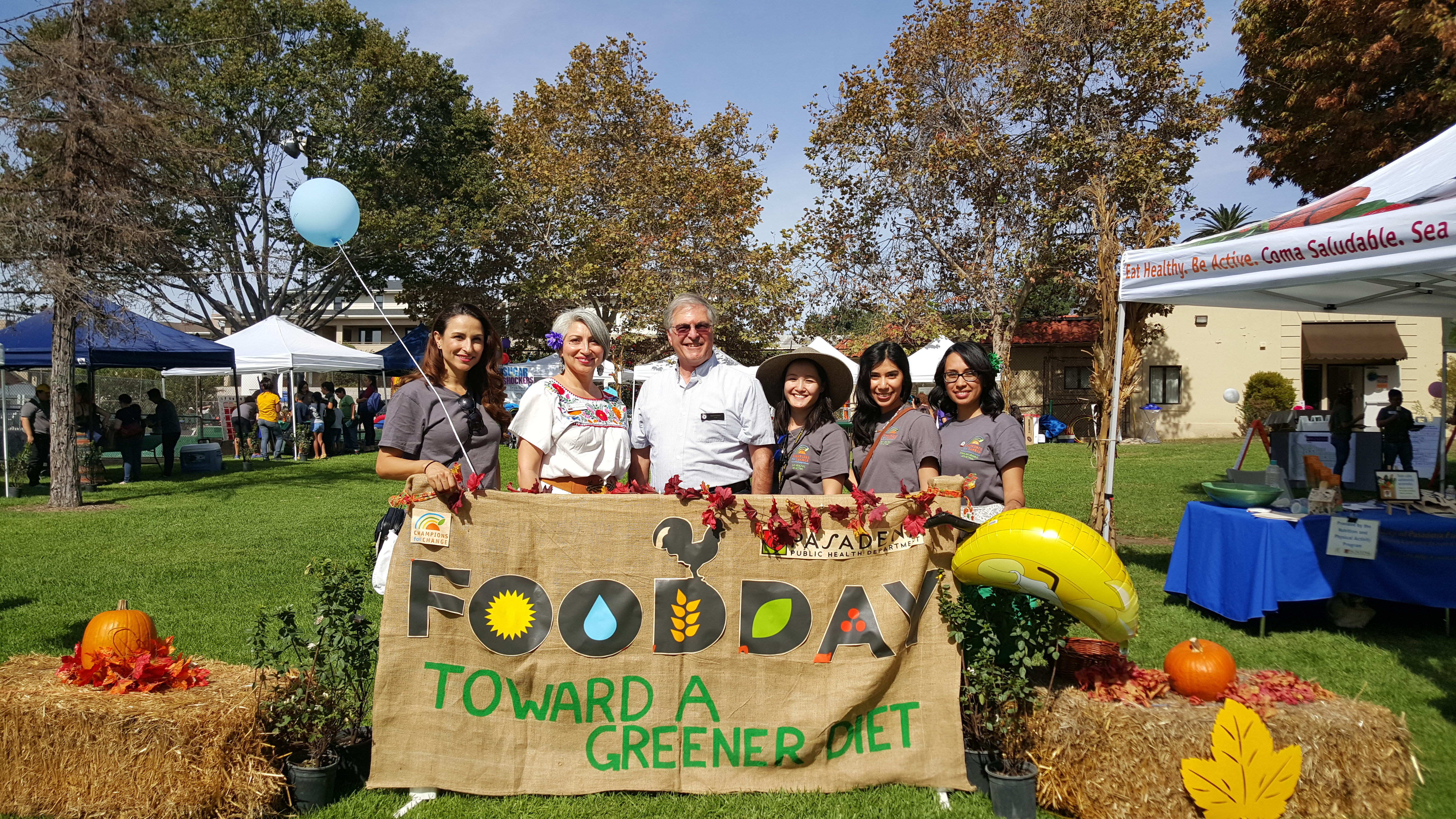 Six people posing behind Food Day banner