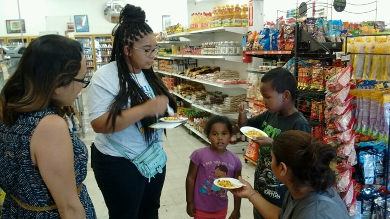 Three women and two children eating in store aisle