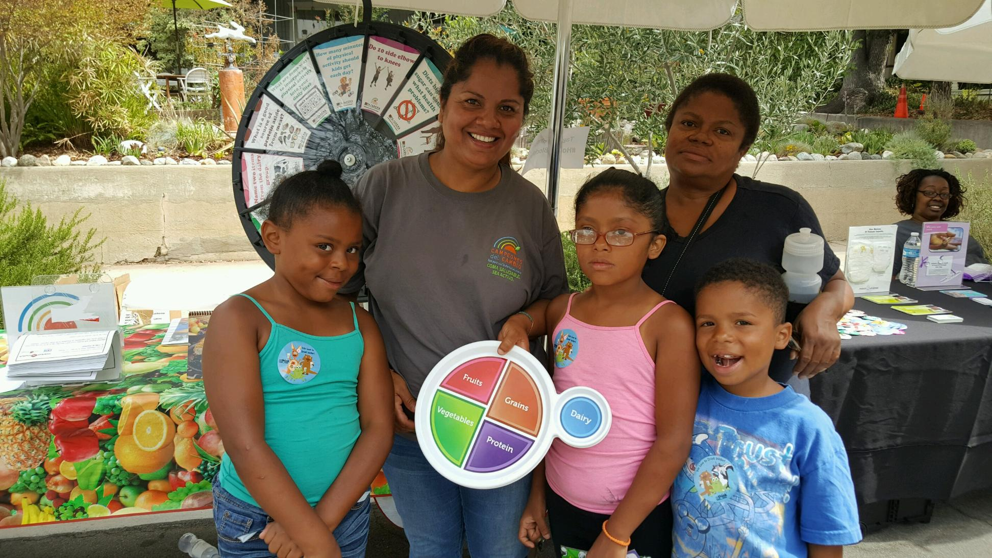 Two women and three children in front of factoid wheel