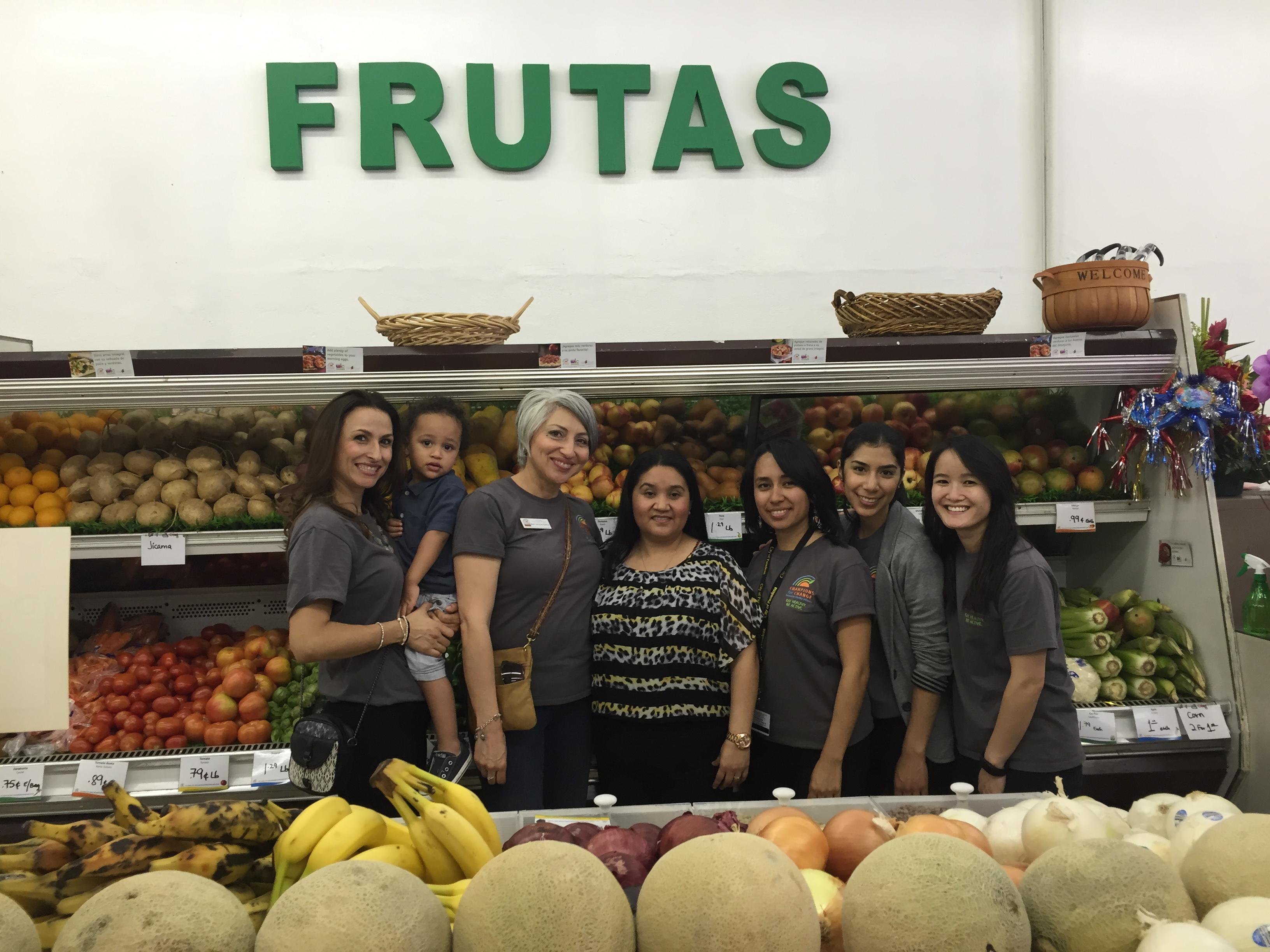 Women posing under Frutas sign