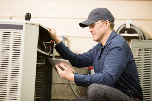 Repairmen works on a home's air conditioner unit outdoors. He is checking the compressor inside the unit using a digital tablet. He wears a navy blue uniform and his safety glasses.