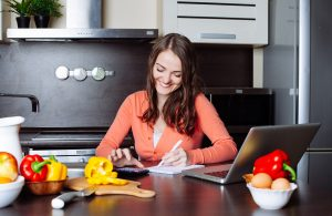 Happy young woman is doing banking and administrative work holding bills at home