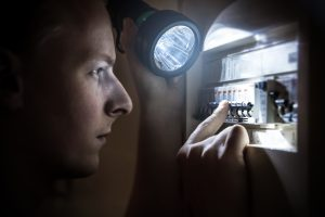 close-up of man with flashlight looking at breaker