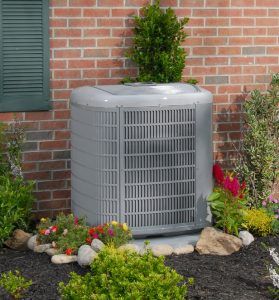 Central AC in backyard in front of brick wall