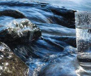 image of glass of water in front of river