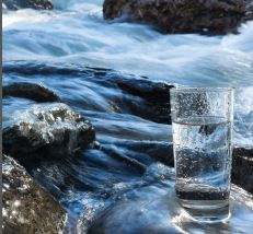 image of a glass of water with a river behind