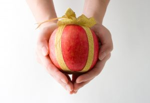human hand holding an apple wrapped as a gift
