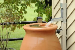 Rain barrel being filled with water from gutters during rain storm.