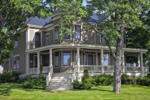 Classic older north American home surrounded by shady trees.