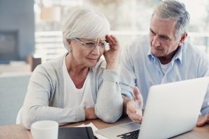 older woman with hand on head looking at laptop with another older man