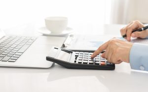 Businessman using a calculator to calculate the numbers. Accounting , Accountancy, Calculation Concept.