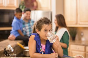 Loving Hispanic family cooks dinner together in home kitchen. Daughter foreground drinks water in clear glass.