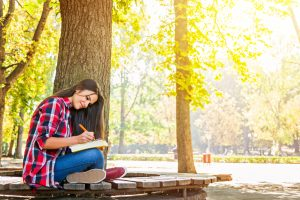 girl in plaid red shirt and jeans writting in a book on a bench in park