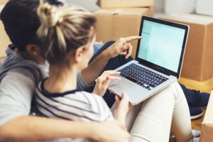 Young couple sitting between boxes and using a laptop. image of couple is blury with the focus on the laptop
