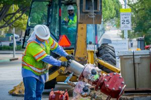 water utility workers holding a water main, utility worker in a backhoe