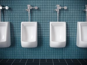 Four urinals on a blue tiled wall in public restroom. Very high resolution
