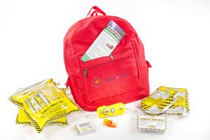 red backpack with a variety of things you'd need in an emergency like water and food