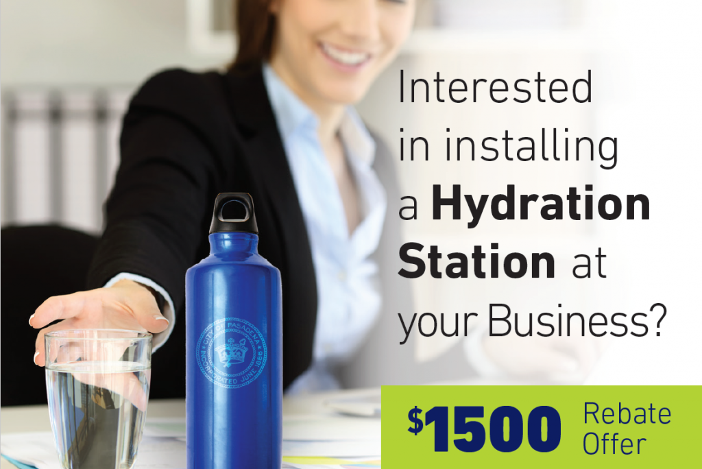 """A woman reaches for a glass of water that is sitting next to a PWP water bottle. Text reads """"Interested in installing a Hydration Station at your Business? $1500 Rebate Offer"""""""